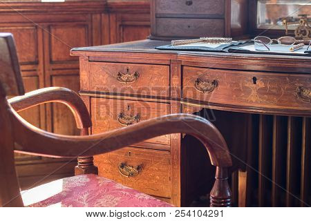 Fine antique pedestal writing desk and chair. Studying history and period drama. Ornate regency table with reading and author materials. Magnifying glass, glasses or spectacles, and fountain pen. stock photo