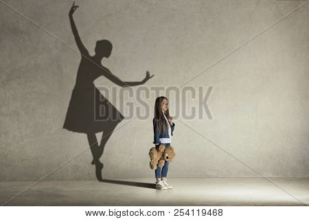 Baby Girl Dreaming About Dancing Ballet. Childhood And Dream Concept. Conceptual Image With Shadow O
