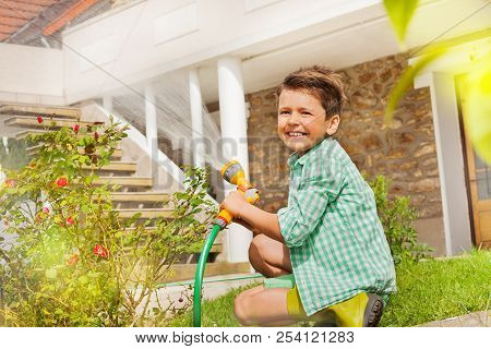 Little gardener watering plants at the backyard stock photo