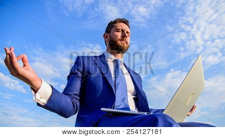 Man try keep his mind clear. Entrepreneur find minute relax and meditate. Work online can be annoying. Communication online full of bullying. Businessman formal suit with laptop meditating outdoors stock photo