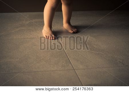 Barefoot baby are staying on heating tile floor. stock photo
