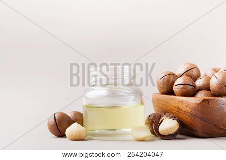 Jar with macadamia oil and bowl with nuts on table. stock photo