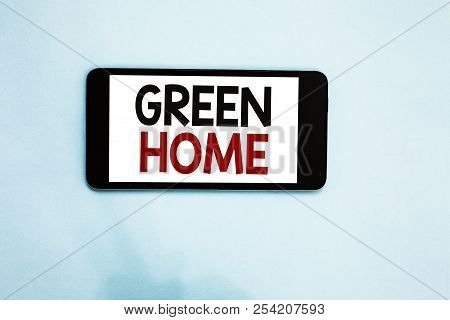 Text sign showing Green Home. Conceptual photo An area filled with plants and trees where you can relax Cell phone white screen over light blue background text messages apps. stock photo