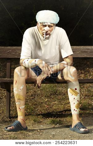 Wounded and treated man relaxing after accident on park bench stock photo