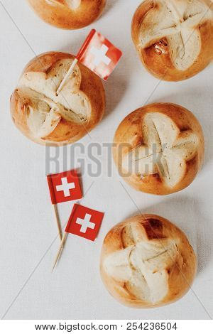 Traditional swiss bread buns called in German 1.Augustweggen baked in Switzerland to celebrate Swiss National Day on August 1st. The top of the bread being cut crosswise to shape a cross as symbol of Switzerland. Swiss flags on wooden toothpicks.  White b stock photo