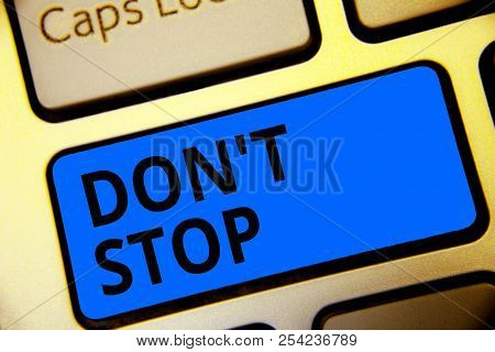 Writing note showing Don t not Stop. Business photo showcasing Continue what had been doing without rendering a delay Keyboard blue key Intention computer computing reflection document. stock photo