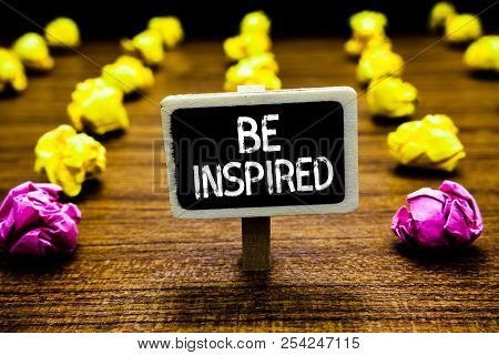 Text sign showing Be Inspired. Conceptual photo extraordinary quality as arising from some creative impulse Blackboard crumpled papers several tries mistake not satisfied wooden floor. stock photo