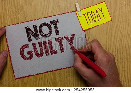 Word writing text Not Guilty. Business concept for someone is innocent didnt commit specific crime He free Man holding marker paper clothespin reminder express ideas wooden table. stock photo