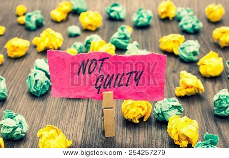 Writing note showing Not Guilty. Business photo showcasing someone is innocent didnt commit specific crime He free Clothespin holding pink note paper crumpled papers several tries. stock photo