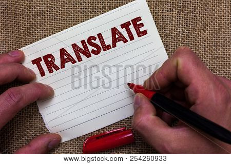 Writing note showing Translate. Business photo showcasing Another word with same equivalent meaning of a target language Man's hand hold white paper with symbolic letter jute sack background stock photo