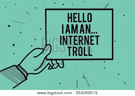 Text sign showing Hello I Am An ... Internet Troll. Conceptual photo Social media troubles discussions arguments Man hand holding paper communicating information dots turquoise background. stock photo