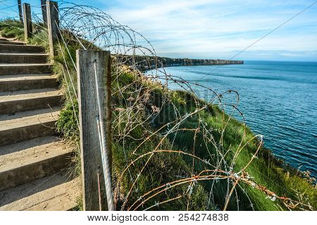 The coast of Normandy France, Pointe du hoc where the allied forces faced the Germans during World War 2, with barbed wire, the cliffs and the sea stock photo
