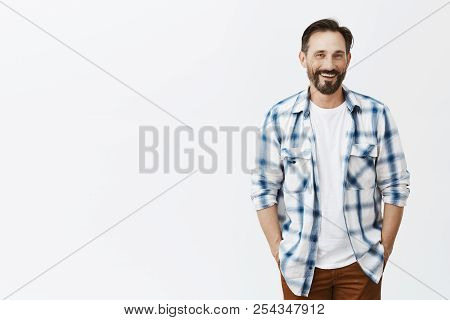 Best grandad ever. Portrait of joyful handsome mature male with beard, holding hands in pockets and smiling at camera, walking along park with family and enjoying looking kid having fun stock photo