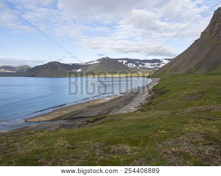 Northern summer landscape, sand bech with view on beautiful snow covered cliffs and Alfsfell mountain, Hloduvik cove in Hornstrandir, west fjords, Iceland, green meadow, blue sky background stock photo