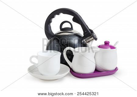 Modern black stainless steel stovetop kettle with steam whistle built-in in spout and cup on saucer, sugar bowl, creamer on a white background stock photo