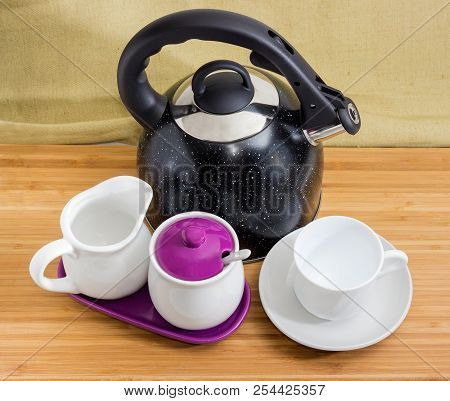 Modern black stainless steel stovetop kettle with steam whistle built-in in spout and empty cup on saucer, sugar bowl, creamer on a bamboo wooden surface stock photo