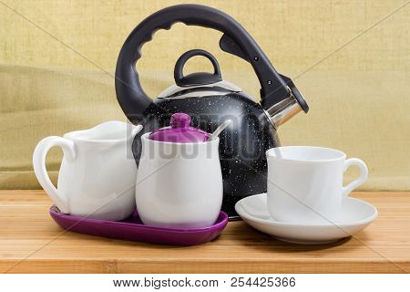 Modern black stainless steel stovetop kettle with steam whistle built-in in spout and cup on saucer, sugar bowl, creamer on a bamboo wooden surface stock photo