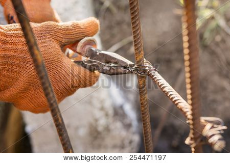 Hands of the builder in orange gloves, twisting the armature with wire using pliers stock photo