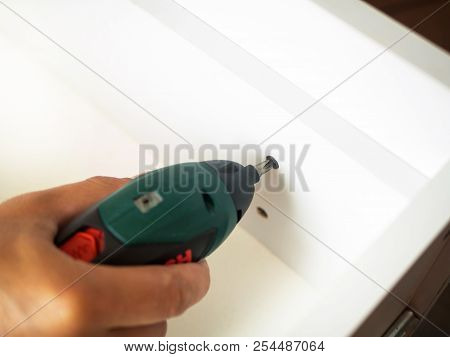 Man hand holding electric screwdriver and screwing screw in the wooden furniture box. close up shot, DIY stock photo
