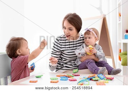 Young nanny playing with cute little children at table, indoors stock photo