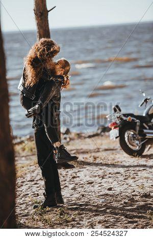 man holding his girlfriend on arms on seashore with cruiser bike near stock photo