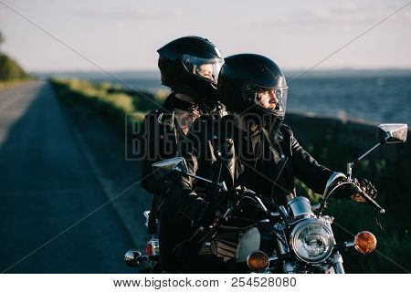 Couple Of Bikers In Helmets Riding Classical Motorcycle On Country Road