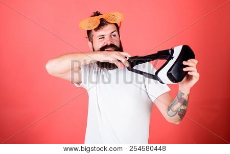 Man bearded hipster with virtual reality headset and louvered sunglasses red background. Alternative reality addiction. Get rid of virtual games addiction. Man throws out virtual reality headset. stock photo