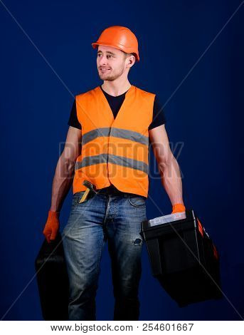 Handyman, repairman on smiling face carries heavy bags with professional equipment. Man in helmet, hard hat holds toolbox and suitcase with tools, blue background. Professional repairman concept. stock photo