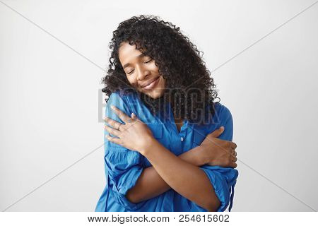 Self love concept. Isolated shot of beautiful pleased young dark skinned female with voluminous hairstyle embracing herself and closing eyes, enjoying soft fabric of her new stylish blue shirt stock photo
