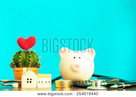 Piggy Bank and home model and gold coin and cactus with red heart and stethoscope put on the desk on blue wall background, Loans for real estate or save money for buy a new house to family concept. stock photo