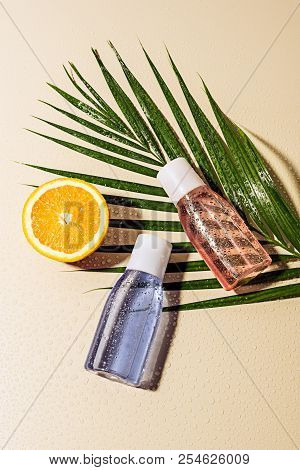 flat lay with micellar water in bottles, green palm leaf and orange half with water drops on beige backdrop stock photo
