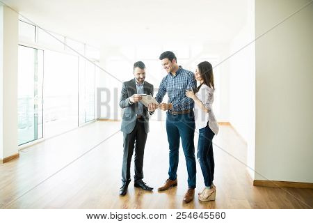 Mid adult of couple signing sale purchase agreement held by broker in new home stock photo