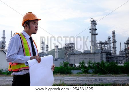 The engineer is working with tabet on large industry background. The construction manager on the industry background. stock photo