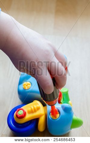 A little child is collecting a toy motorcycle at home on the floor. Children's fingers skillfully operate with colored plastic details of a plaything. The kid is studying colors during the playing. stock photo