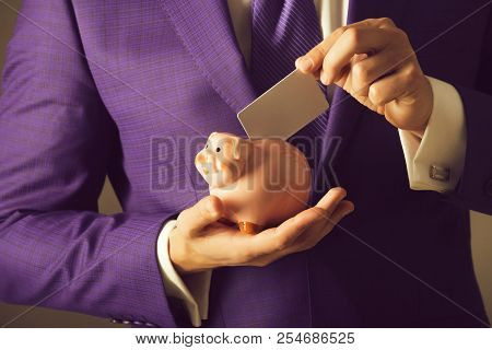 hands putting blank business card in piggy bank for saving on grey background. Stylish formal blue suit and tie. Banking, money, loan, moneybox, ecash and information stock photo
