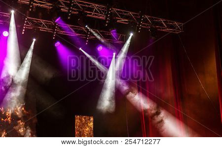 Stage lights. Several projectors in dark. A bright colored spotlight permeates the darkness. Light from the stage, rock concert. Lighting equipment. Several projectors on theatrical lighting system stock photo