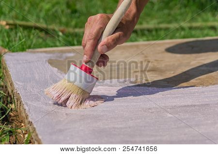 Workers hand  holding a brush and puts primer on concrete floor. Garden repairs and construction. stock photo
