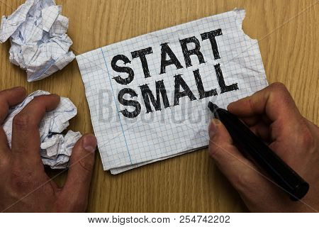 Writing note showing Start Small. Business photo showcasing Small medium enterprises start up Business entrepreneurship Man holding marker notebook paper crumpled papers several tries. stock photo