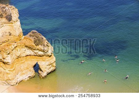Aerial top view of Praia do Camilo beach in Lagos, Algarve region, Portugal. Praia do Camilo is one of the best beaches in Lagos. Famous for the crystal clear water and impressive cliff formations stock photo