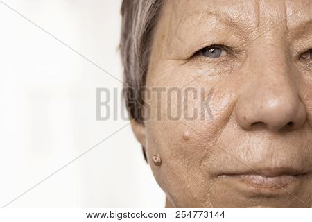 Details of senior woman half face. Elderly pensioner female, cheek close up. stock photo