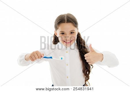 Girl brilliant perfect smile holds toothbrush with drop of paste white background. Child holds toothbrush and shows thumbs up. Child schoolgirl happy face cares mouth hygiene. Brilliant smile concept. stock photo