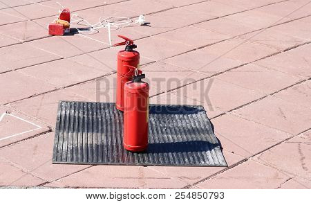 Two red metal large manual carbon dioxide or powder extinguishers for extinguishing a fire stand on a black rubber dielectric rug on the floor. stock photo