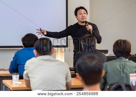 Asian Speaker with casual suit on the stage in low light over the presentation screen in the business or education seminar stock photo