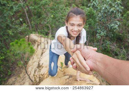 Helping hand - hiker woman getting help on hike smiling happy overcoming obstacle. Tourist walking on the Mountain, Young couple traveling. stock photo