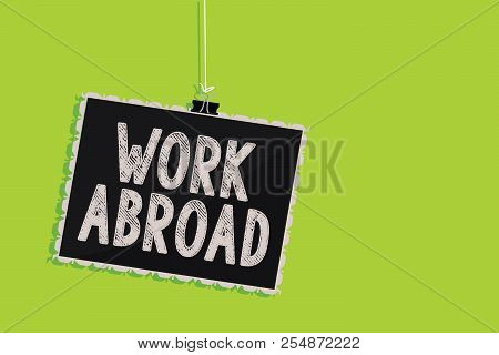 Conceptual hand writing showing Work Abroad. Business photo text Immersed in a foreign work environment Job Overseas Non Local Hanging blackboard message communication sign green background. stock photo