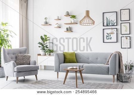 Creative, Wooden Pendant Light Above A Gray Sofa And A Comfy Armchair In A Scandinavian Living Room