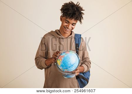 Portrait of a positive young afro american man dressed in hoodie carrying backpack isolated, holding earth globe stock photo