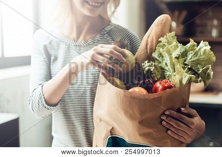 Closeup Of Smiling Girl Holds Bag Of Healthy Food. Close Up Of Beautiful Woman Laying Out Fresh Orga
