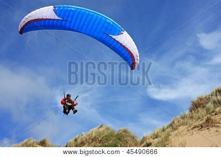 paraglider flying off the dunes of Aberavon beach ** Note: Slight blurriness, best at smaller sizes stock photo