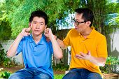 Chinese Asian father conversing with his child however he won't tuning in, holding his ears with his